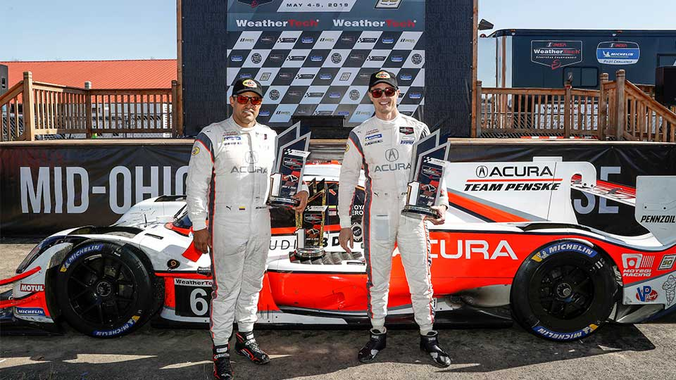 Montoya and Cameron in front of the No. 6 Acura ARX-05 at the Mid-Ohio Sports Car Course Victory Lane